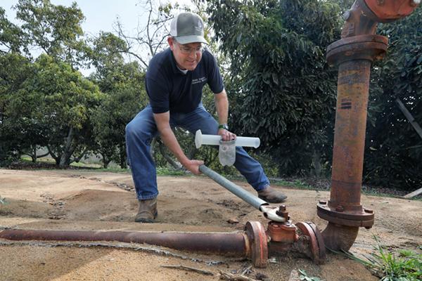 farmer tightening a water main